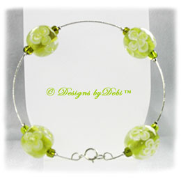 Designs by Debi Handmade Jewelry Aloha Collection Lime Green Silver Bangle Bracelet featuring lime green aloha floral glass beads, lime green seed beads and a spring ring clasp.