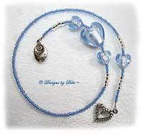 Handmade thong style bookmark in light blue with glass foil heart beads, seed beads, Swarovski crystal bicones, a heart charm and a charm reading Follow your Heart.