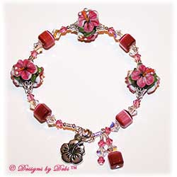 Designs by Debi Handmade Jewelry Aloha Collection Raspberry Hibiscus Bangle Bracelet. Features gorgeous raspberry pink hibiscus handmade lampwork beads, dark pink cat's eye cubes, silver filigree bead caps, swarovski crystal rose and crystal ab bicones, a silver hibiscus charm, dangles and a magnetic clasp